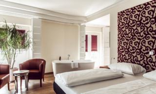 Hotelzimmer mit dunkelroten LEHA-Plissees am Fensterfalz